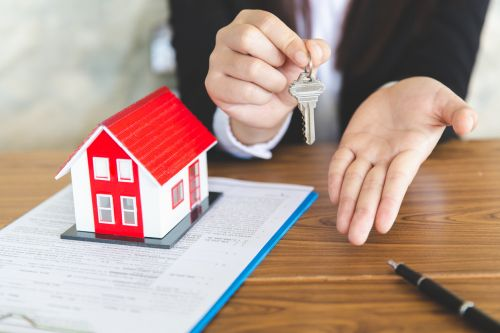 real estate agent holding a house key with a contract